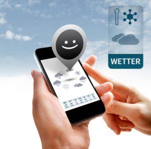 Hands holding smartphone with weather widget